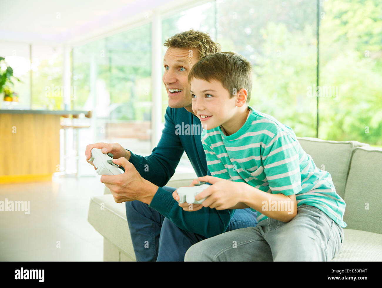 Father and son playing video games in living room Stock Photo