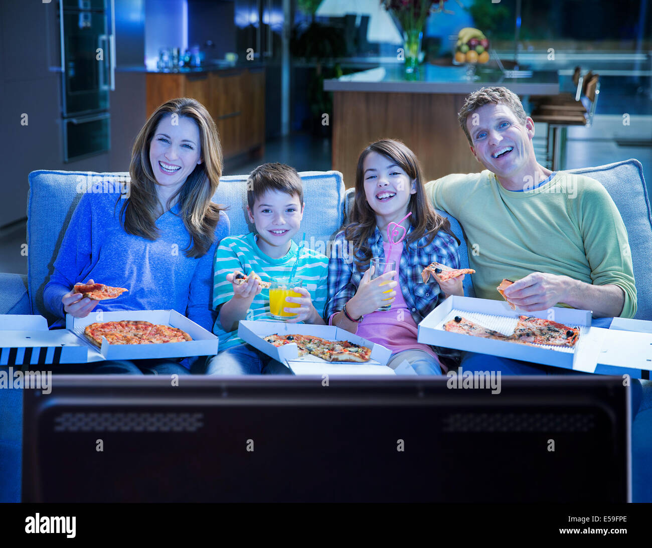 Family eating pizza in front of television in living room - Stock Image