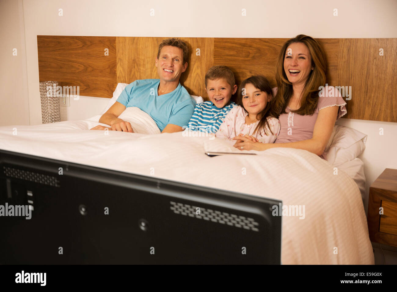 Family watching television in bed - Stock Image