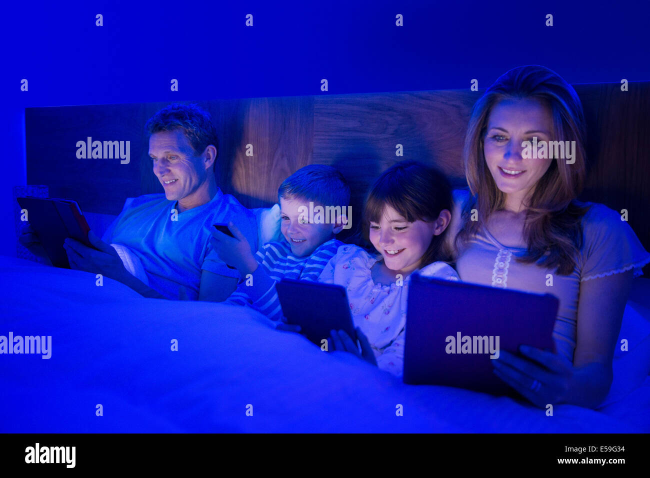 Family using technology in bed - Stock Image