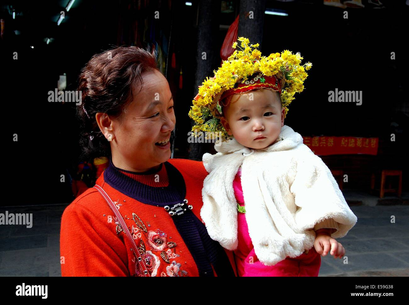 Huang Long Xi, China:  Grandmother with her baby grandson wearing a traditional village floral wreath hat - Stock Image
