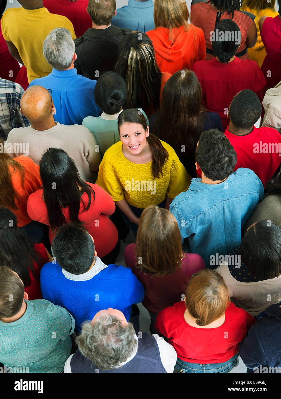 Smiling woman in crowd - Stock Image