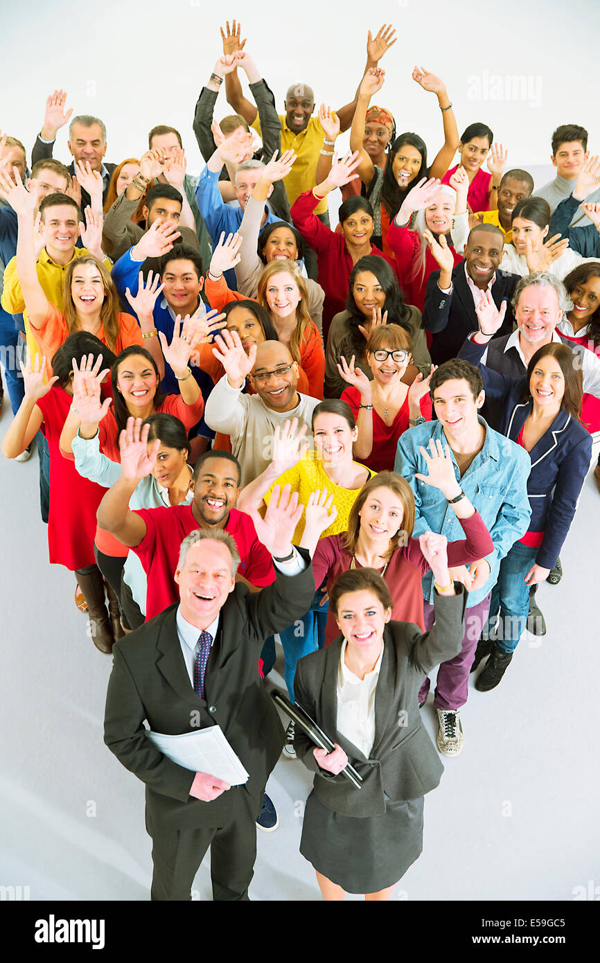 Portrait of diverse workers waving - Stock Image