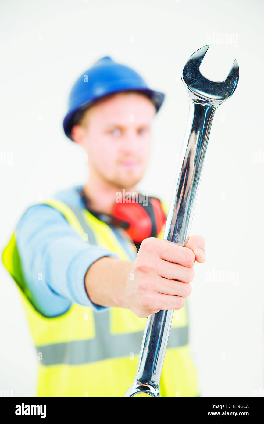 Construction worker holding large wrench - Stock Image