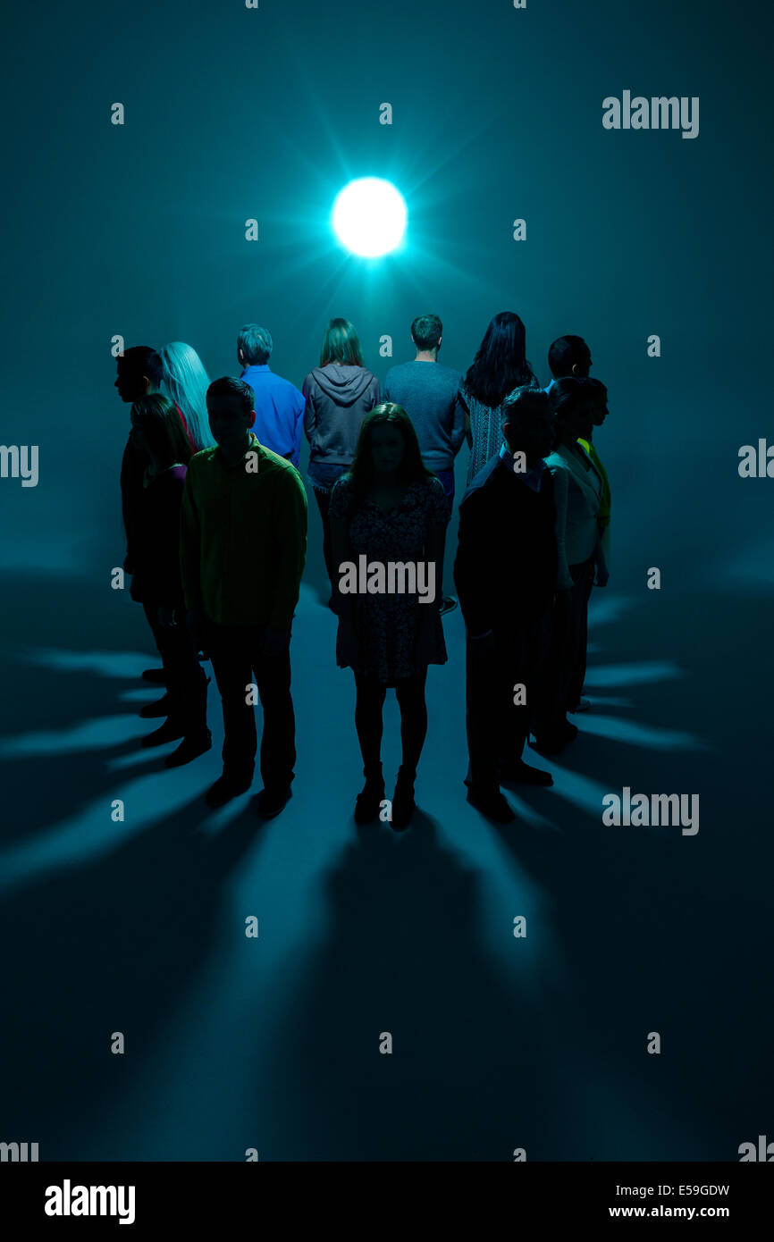 Group with backs to bright light - Stock Image