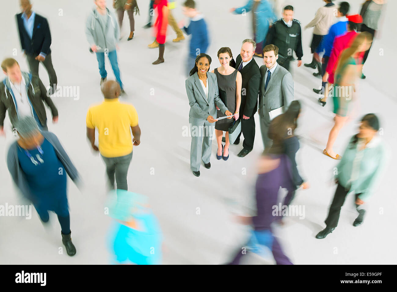 Portrait of business people among bustling crowd - Stock Image