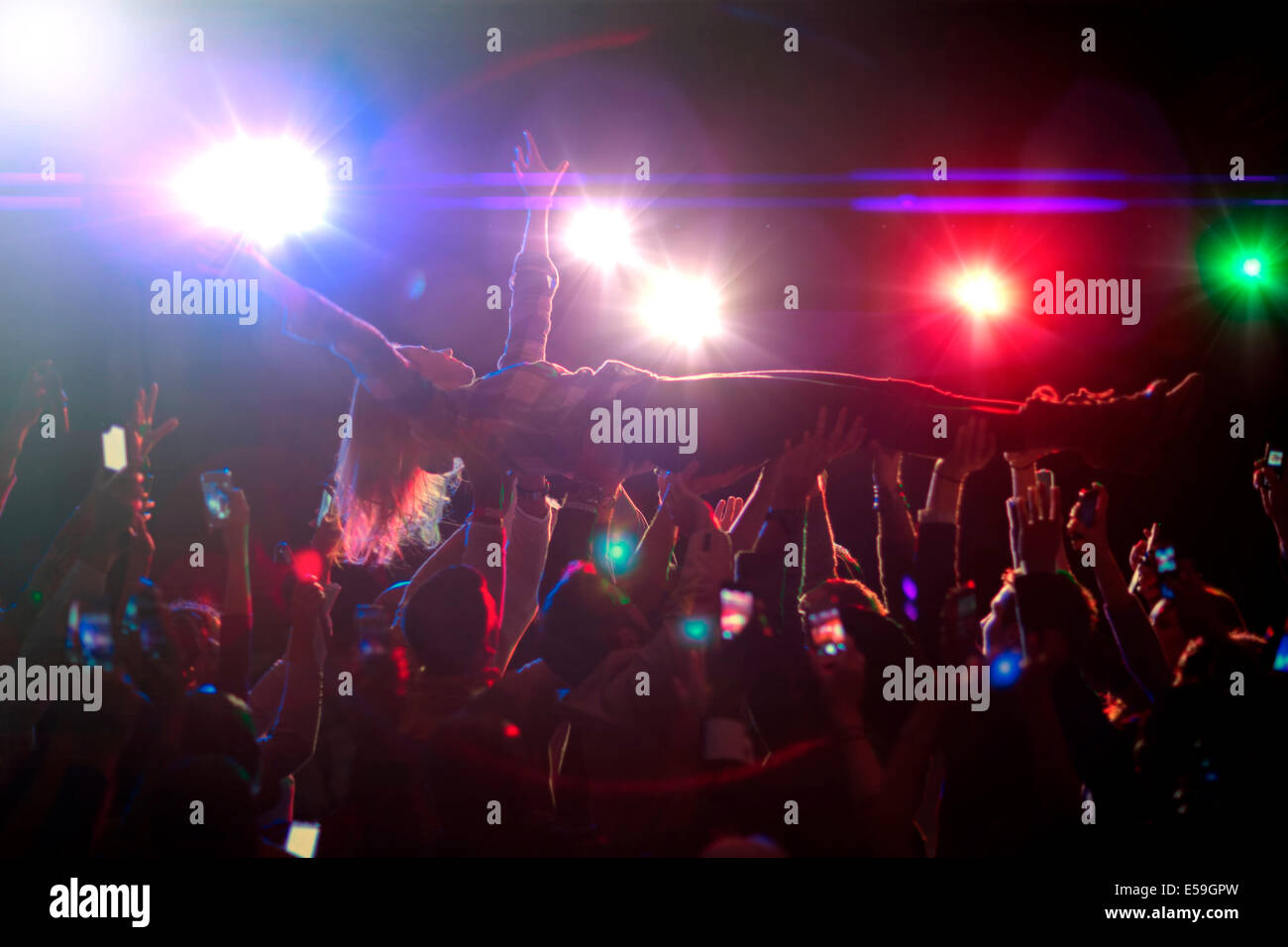 Woman crowd surfing at concert - Stock Image