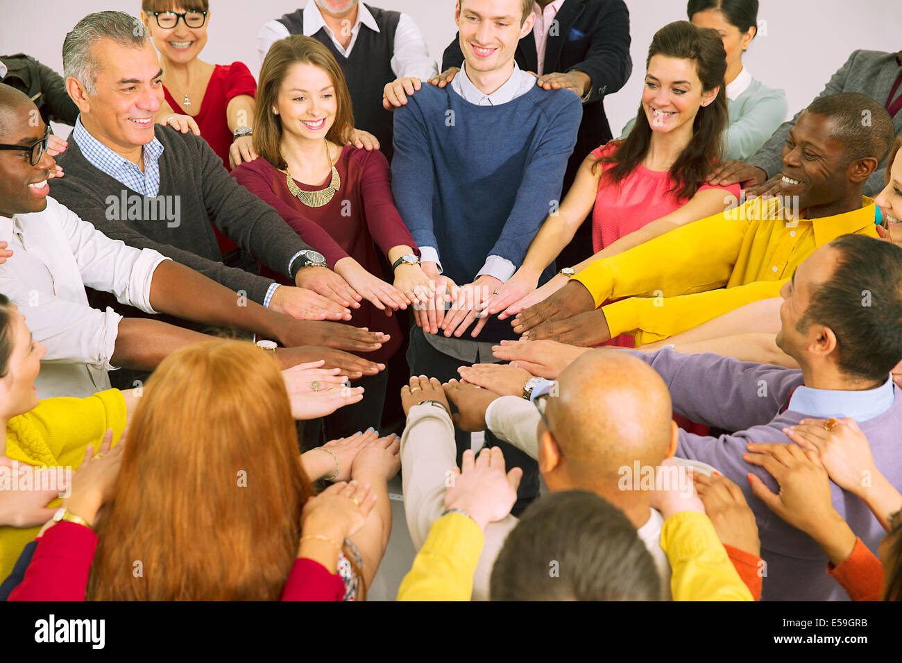 Business people with arms outstretched in huddle - Stock Image