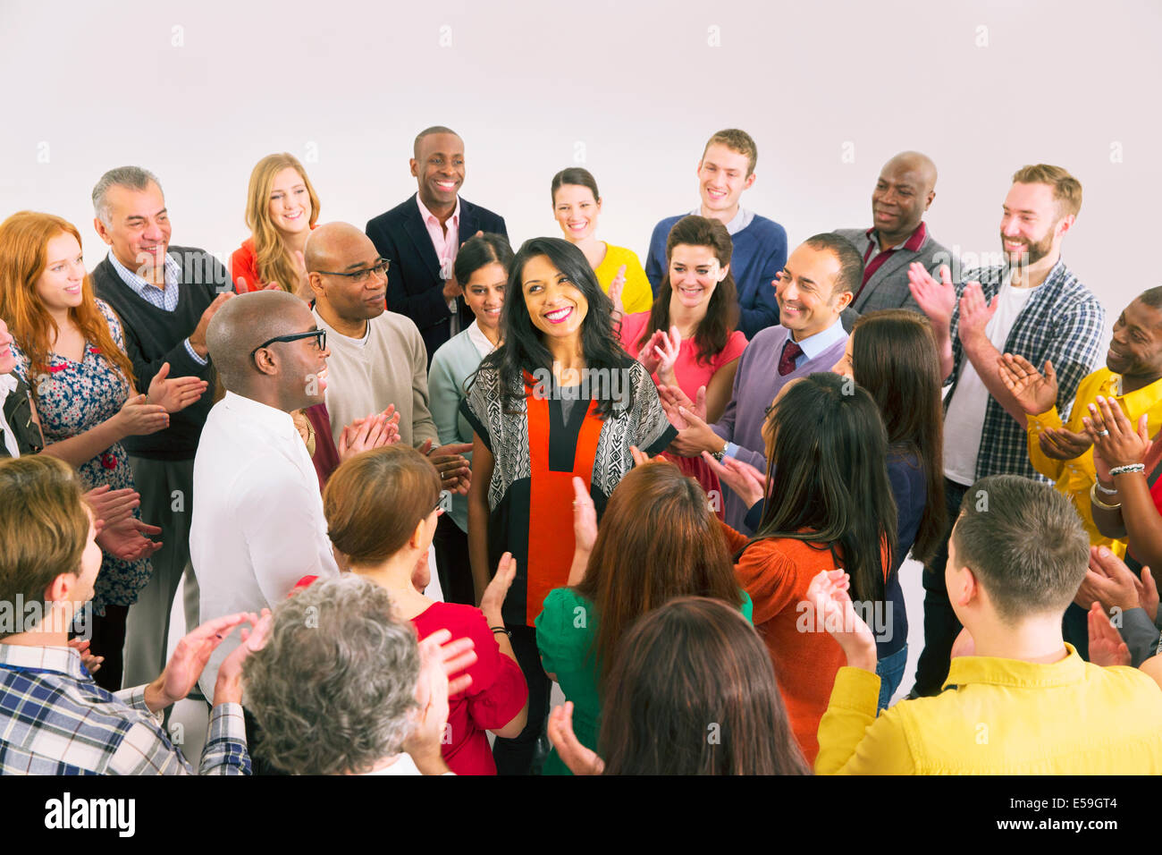 Business people clapping around businesswoman - Stock Image