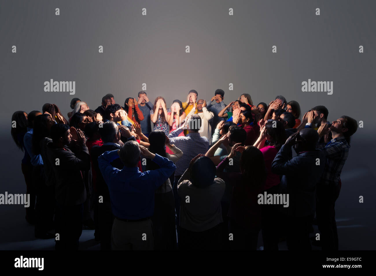 Business people covering eyes around bright light - Stock Image