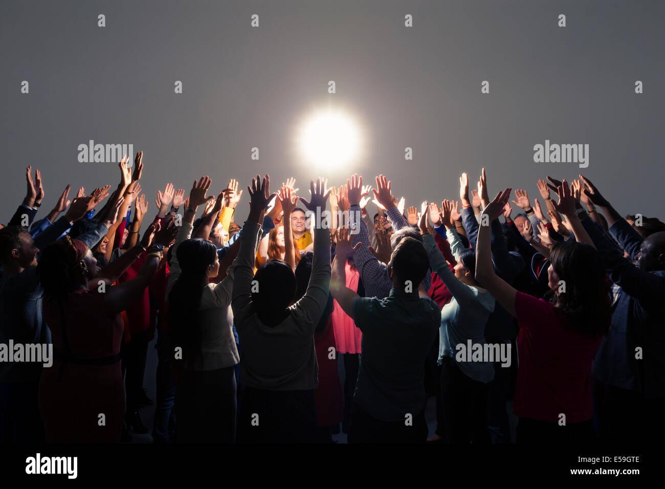 Diverse crowd with arms raised around bright light Stock Photo