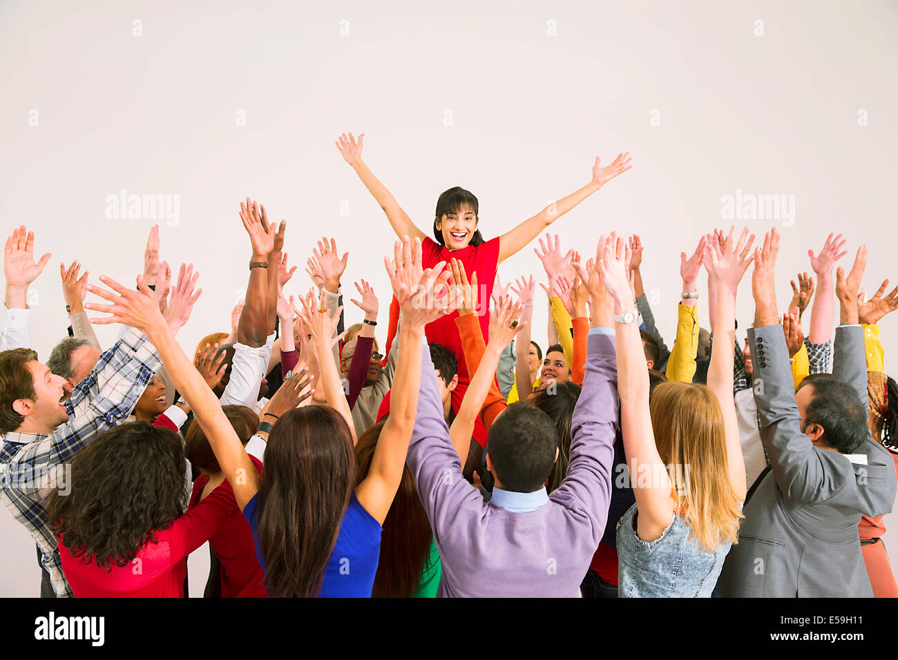 Business people cheering for businesswoman - Stock Image