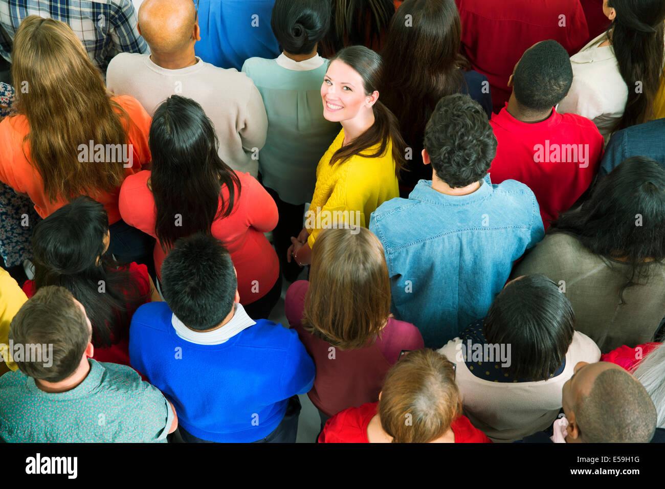 Portrait of confident businesswoman in crowd - Stock Image