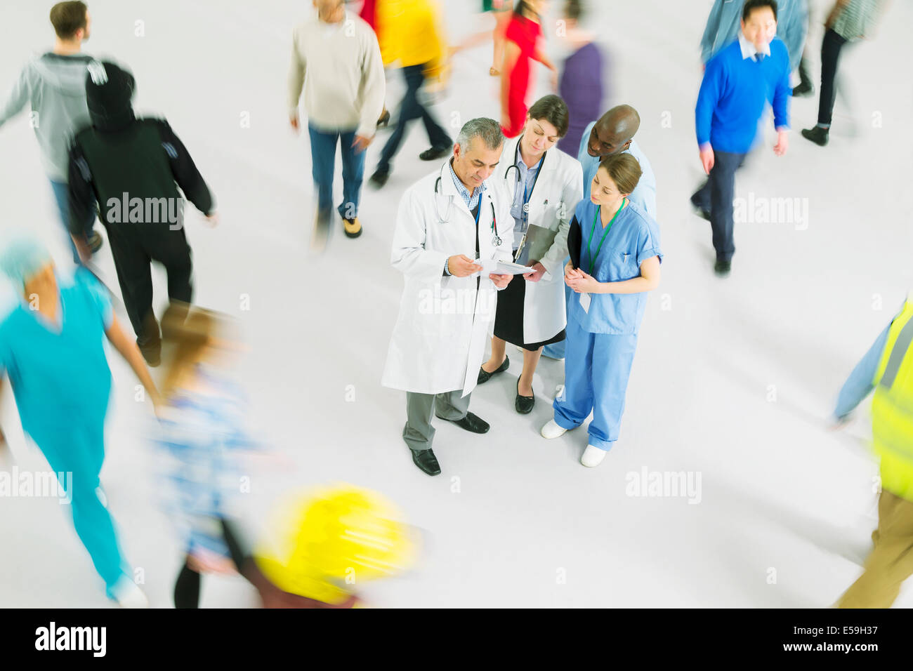 Bustling crowd around doctors and nurses - Stock Image