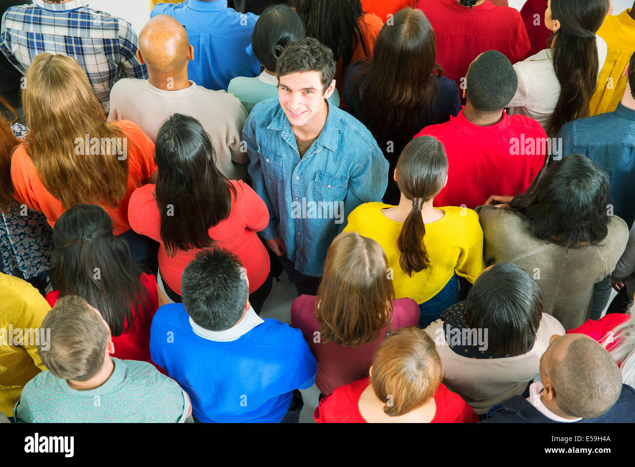 Portrait of smiling man standing out from the crowd - Stock Image