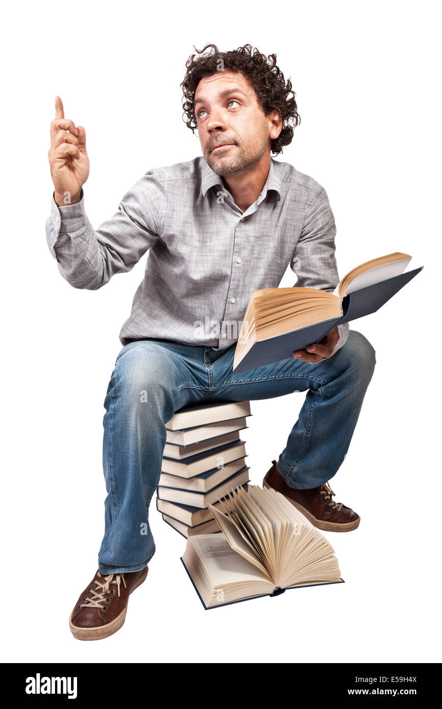 man reading and sit on pile of books - Stock Image