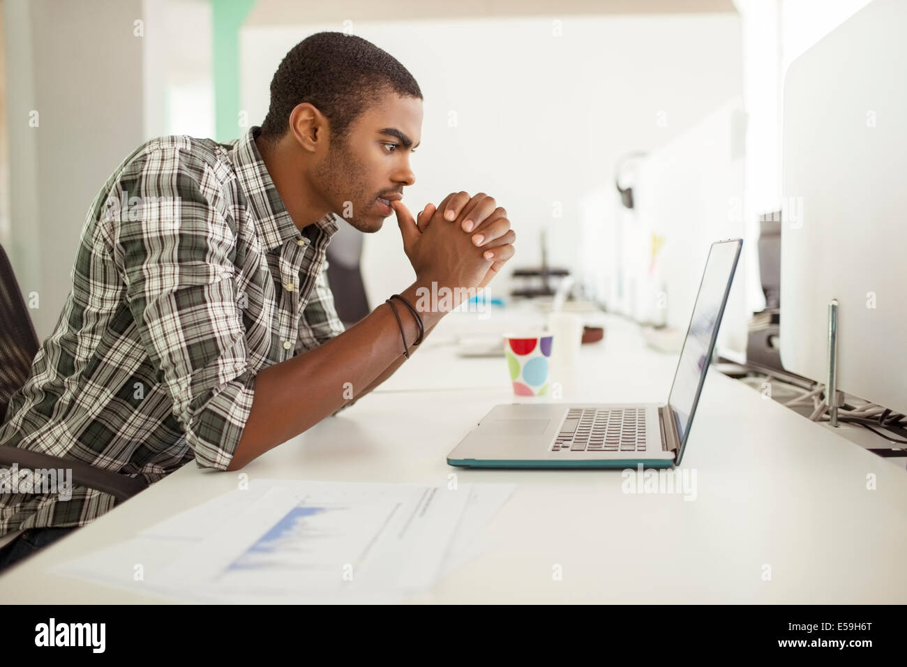 Man working on laptop at office - Stock Image