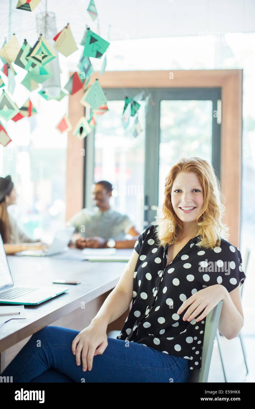 Woman smiling at conference table in office - Stock Image