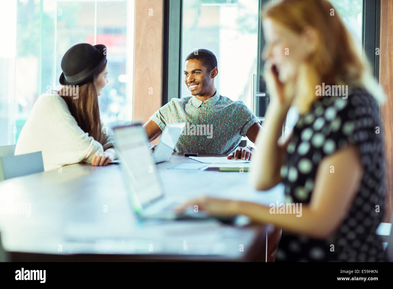 People working at conference table in office - Stock Image