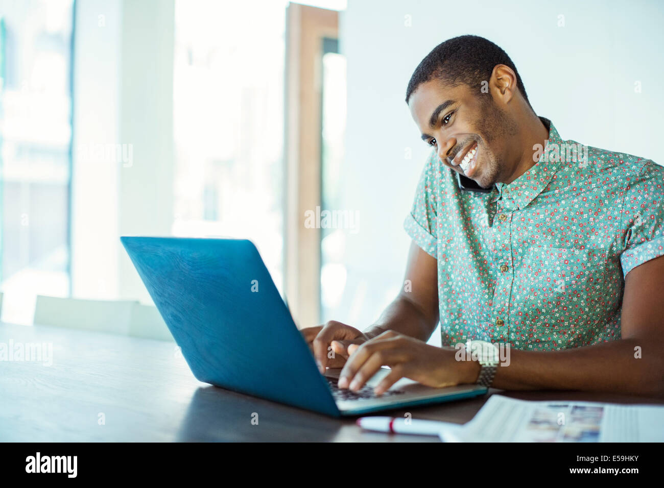 Man using laptop at desk in office - Stock Image