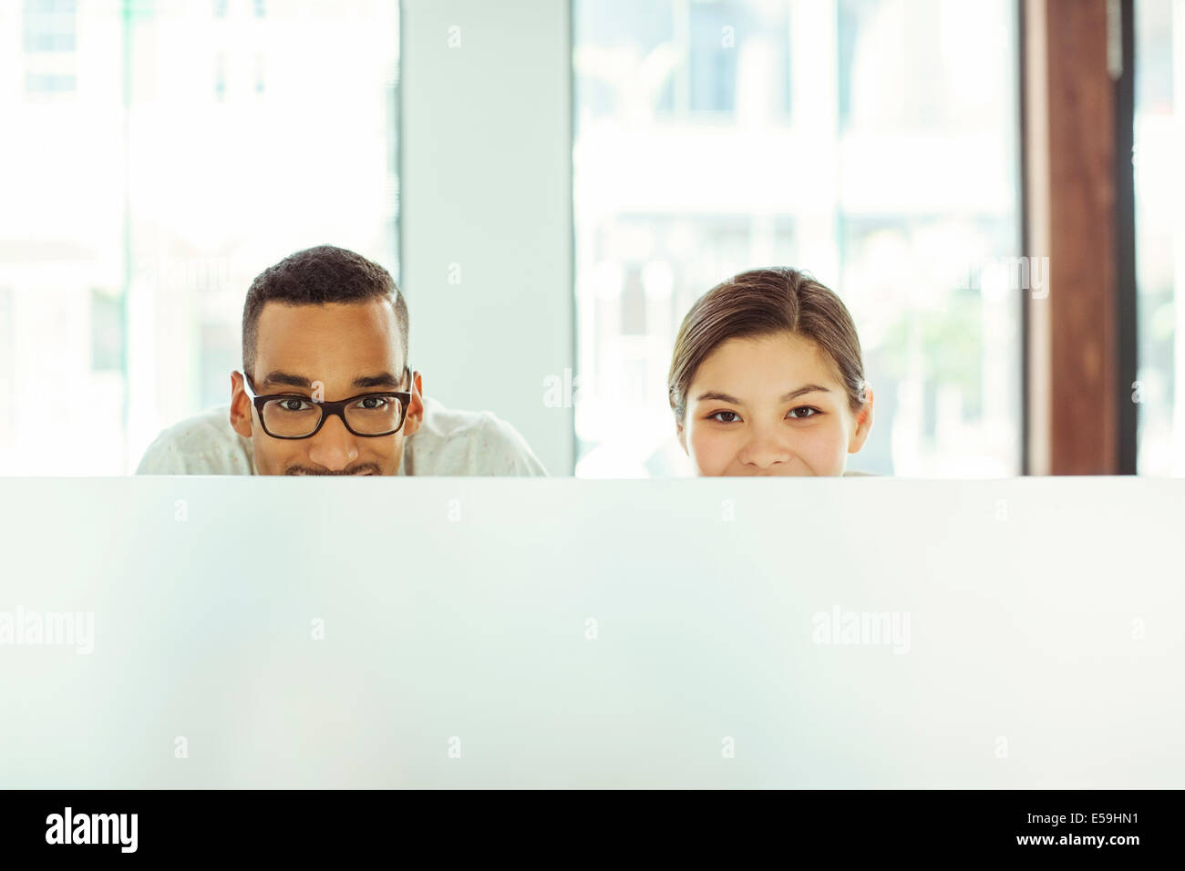 People peering over cubicle in office - Stock Image