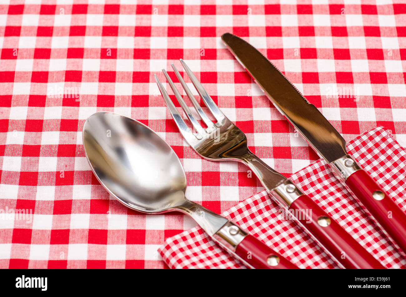Red Silverware On A Red Checkered Napkin And Table Cloth