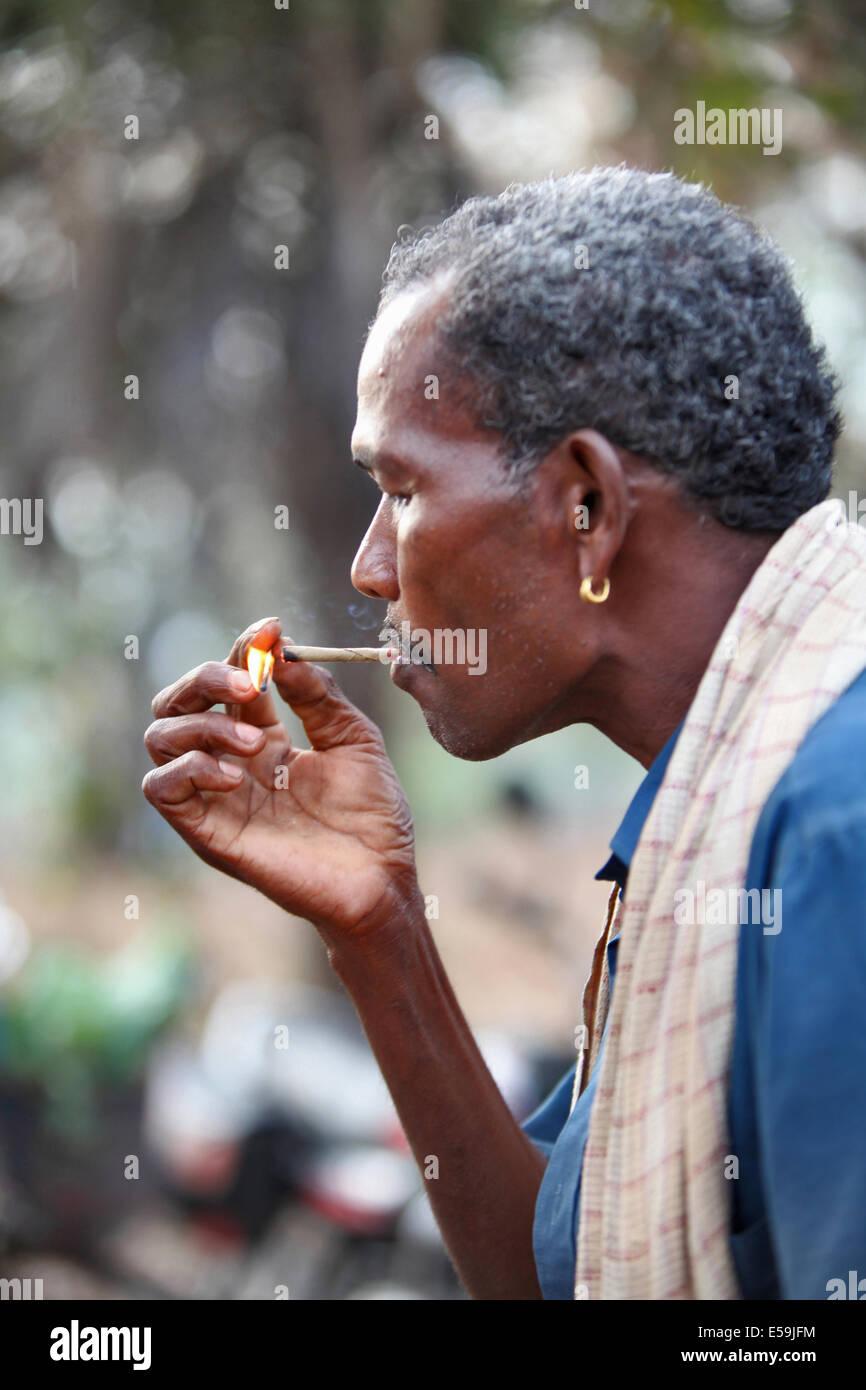 Close-up of a tribal man smoking bidi, an Indian handmade cigarette made of tobacco or beedi leaves, Muriyan Village, - Stock Image