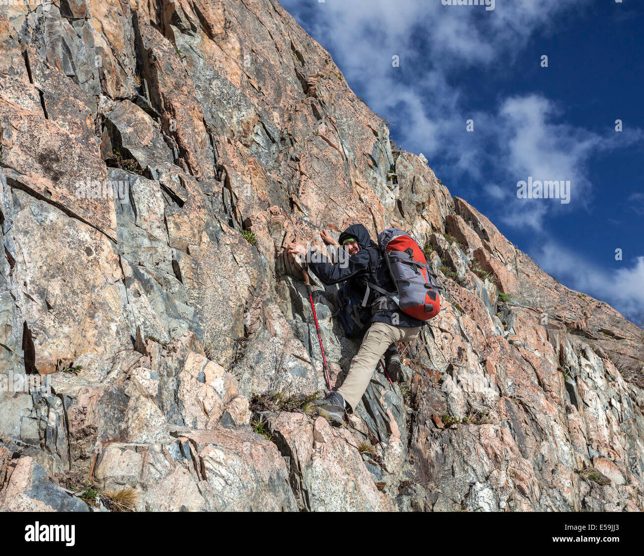 Female hiker climbing with backpack - Stock Image