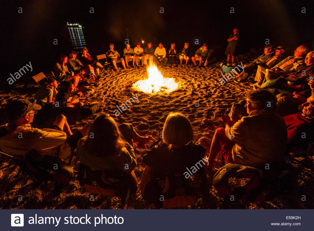 group of people sitting around camp fire mexico stock photo
