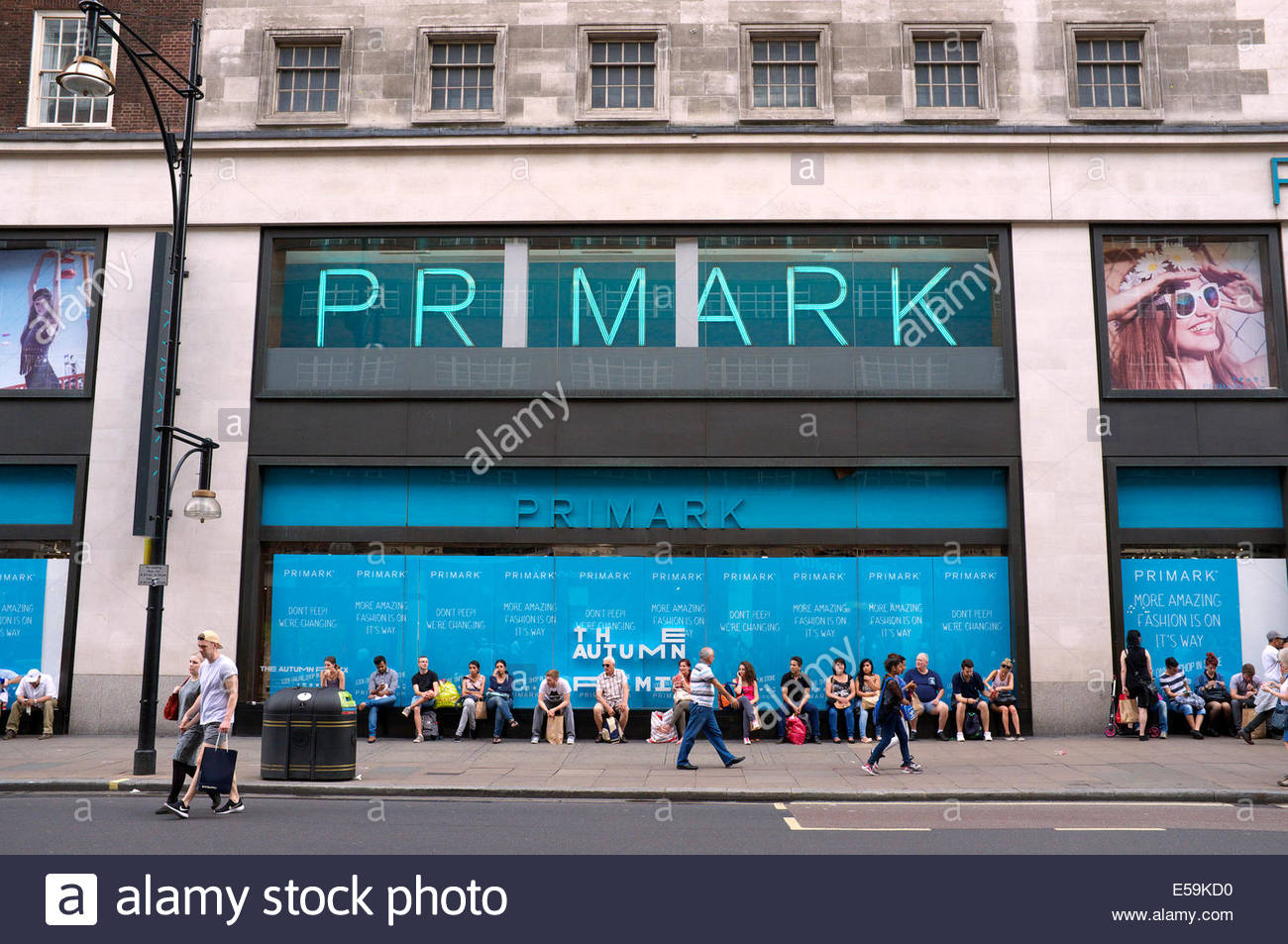 Shoppers rest on the window ledge of the Primark retail store in Oxford Street, London, UK. - Stock Image