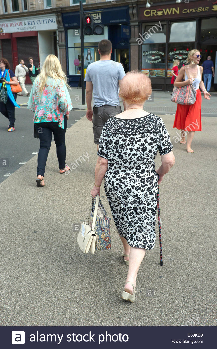 Elderly woman in patterned summer dress, crosses the street with aid of a walking stick, in central London, UK. - Stock Image