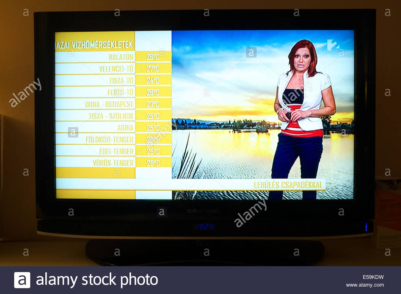 Television weather presenter giving the forecast for Hungary, showing the expected temperatures for different parts - Stock Image