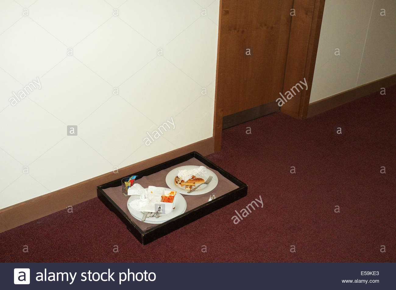A tray with plates that have left over food on, in the corridor outside a hotel room in Budapest, Hungary. - Stock Image