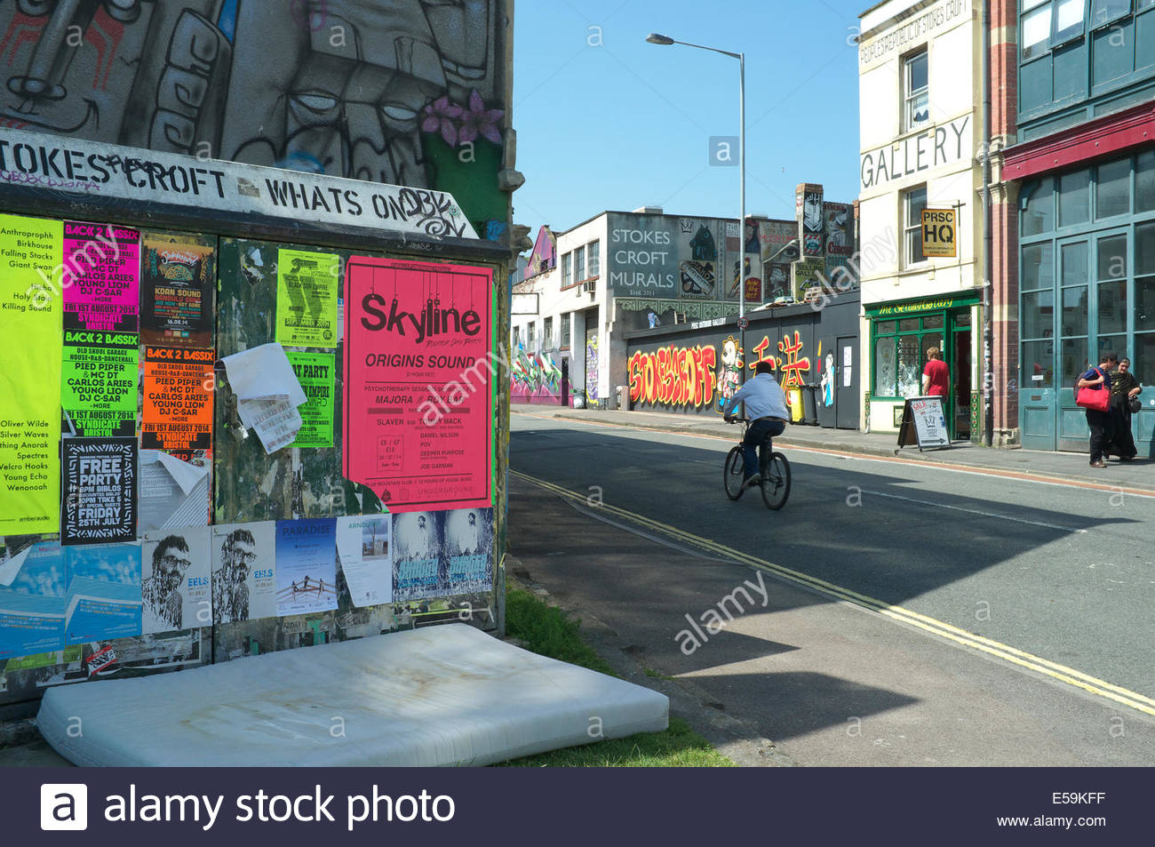 Street scene in Stokes Croft, Bristol, looking down Jamaica Street, and also showing event posters and a discarded - Stock Image
