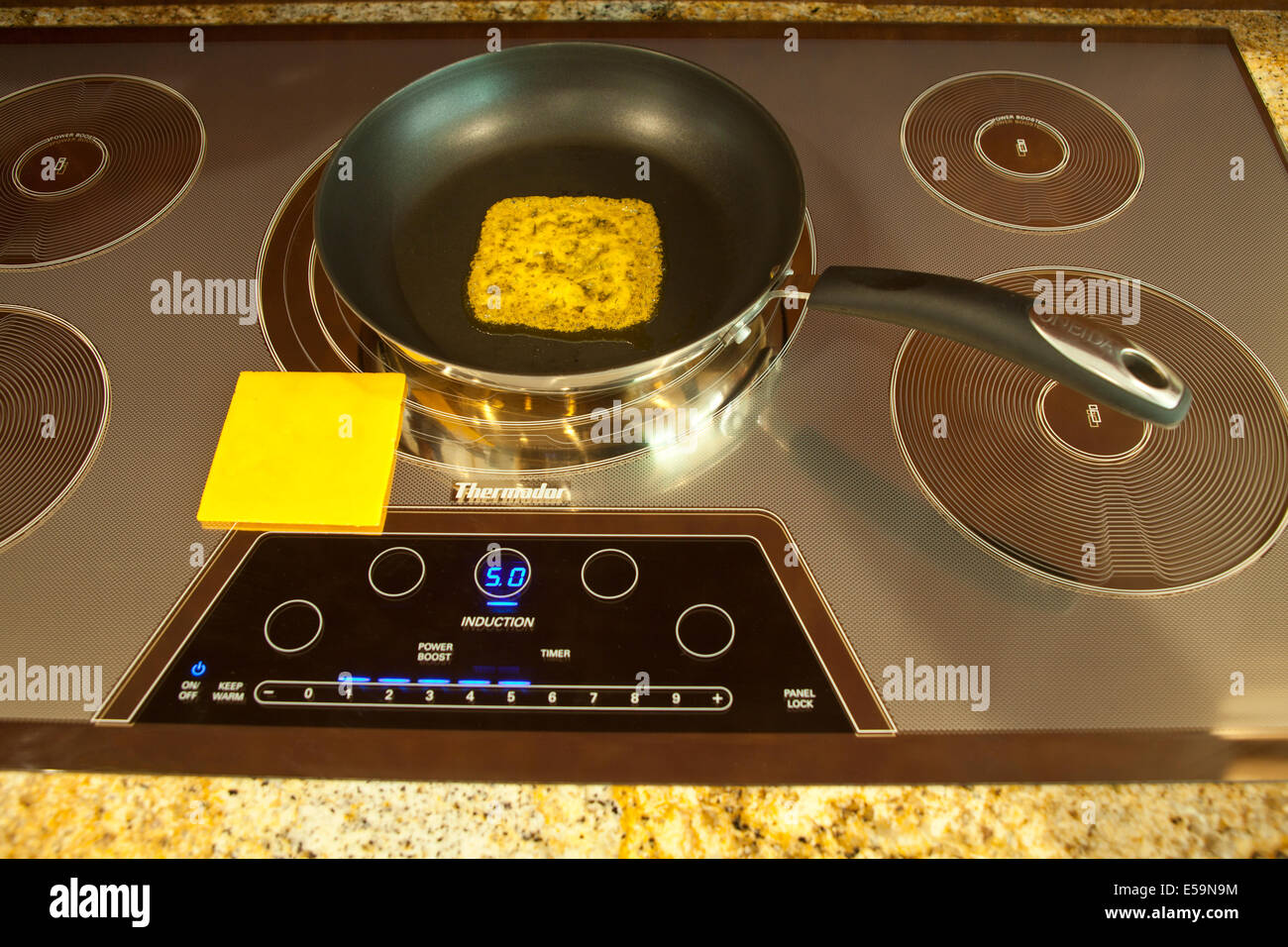 Magnetic energy of Thermador Induction cooktop with melting cheeseMR  Series of 4 images. © Myrleen Pearson - Stock Image