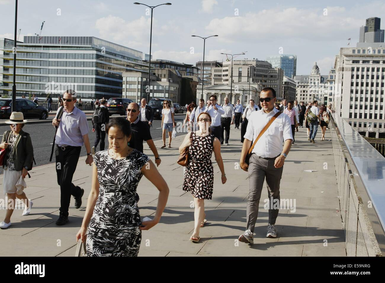 London, UK. 24th July, 2014.   People walk across London bridge as the good weather continues in England. Credit: - Stock Image