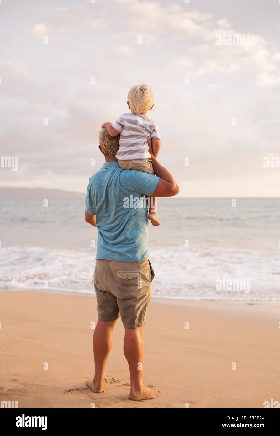 Happy loving father and son on the beach at sunset - Stock Image