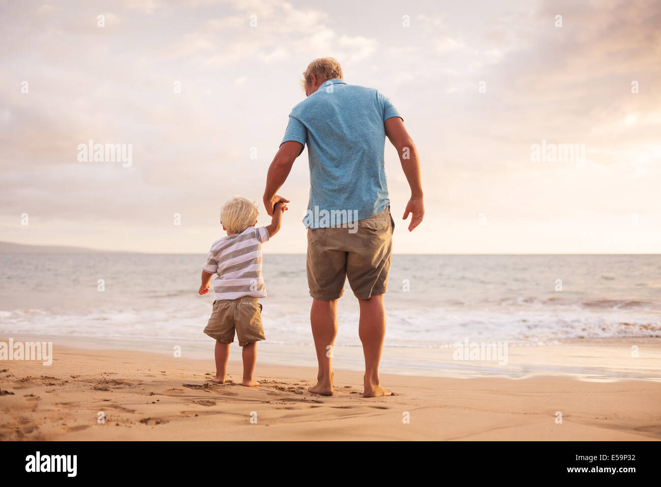 Father and son holding hands walking on the beach at sunset - Stock Image