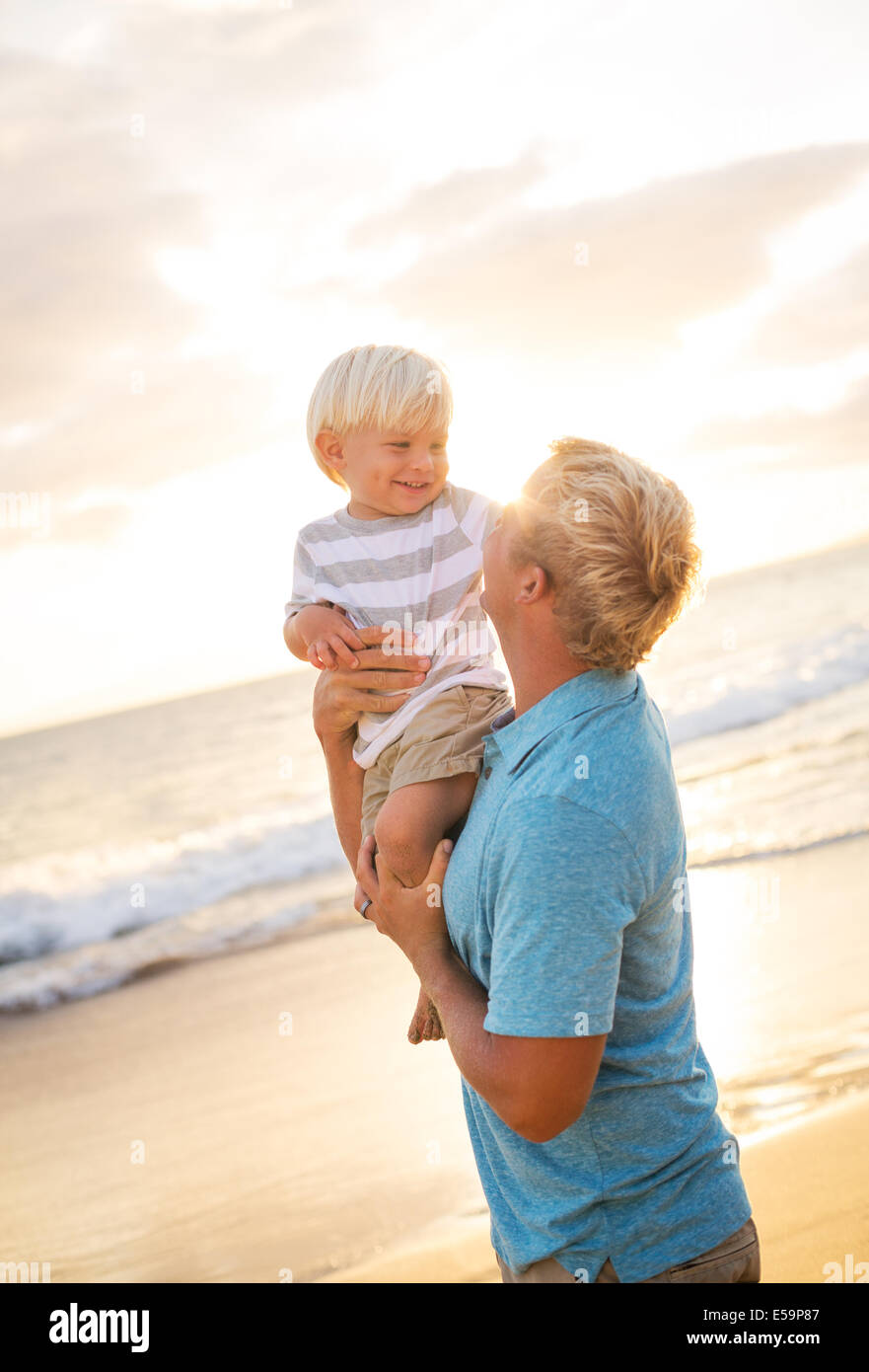 Happy loving father and son on the beach at sunset Stock Photo