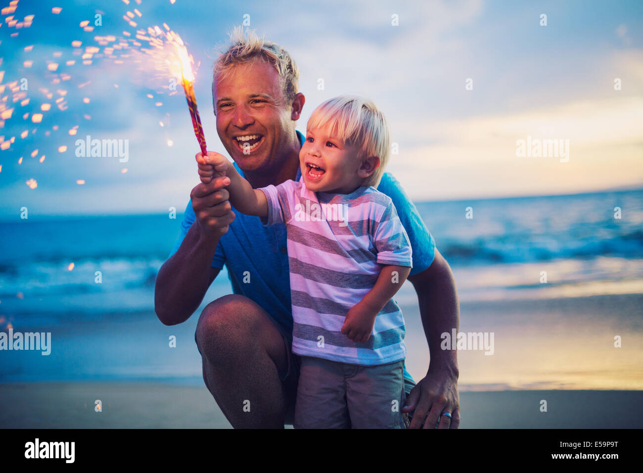 Father and son lighting sparklers on the beach at sunset - Stock Image