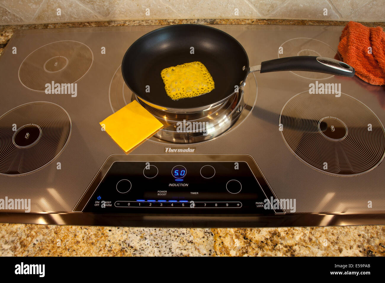 magnetic energy of Thermador Induction cooktop with melting cheese  Series of 4 images. MR  © Myrleen Pearson - Stock Image