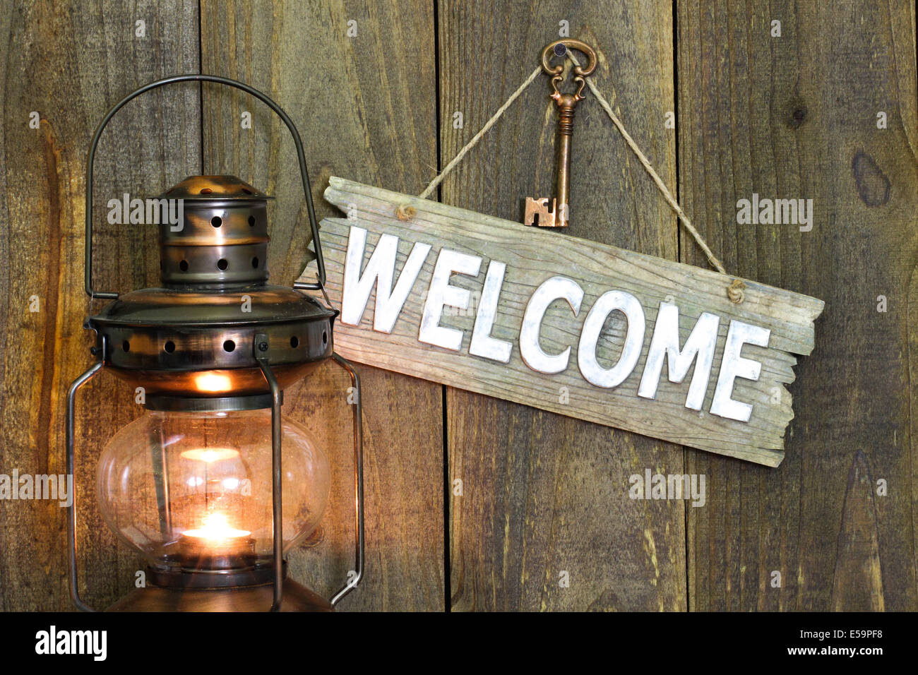 Welcome sign with bronze skeleton key hanging on wooden fence by glowing antique lantern - Stock Image