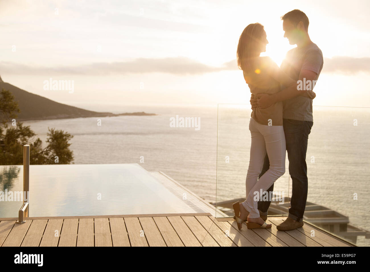 Couple on wooden deck overlooking ocean - Stock Image