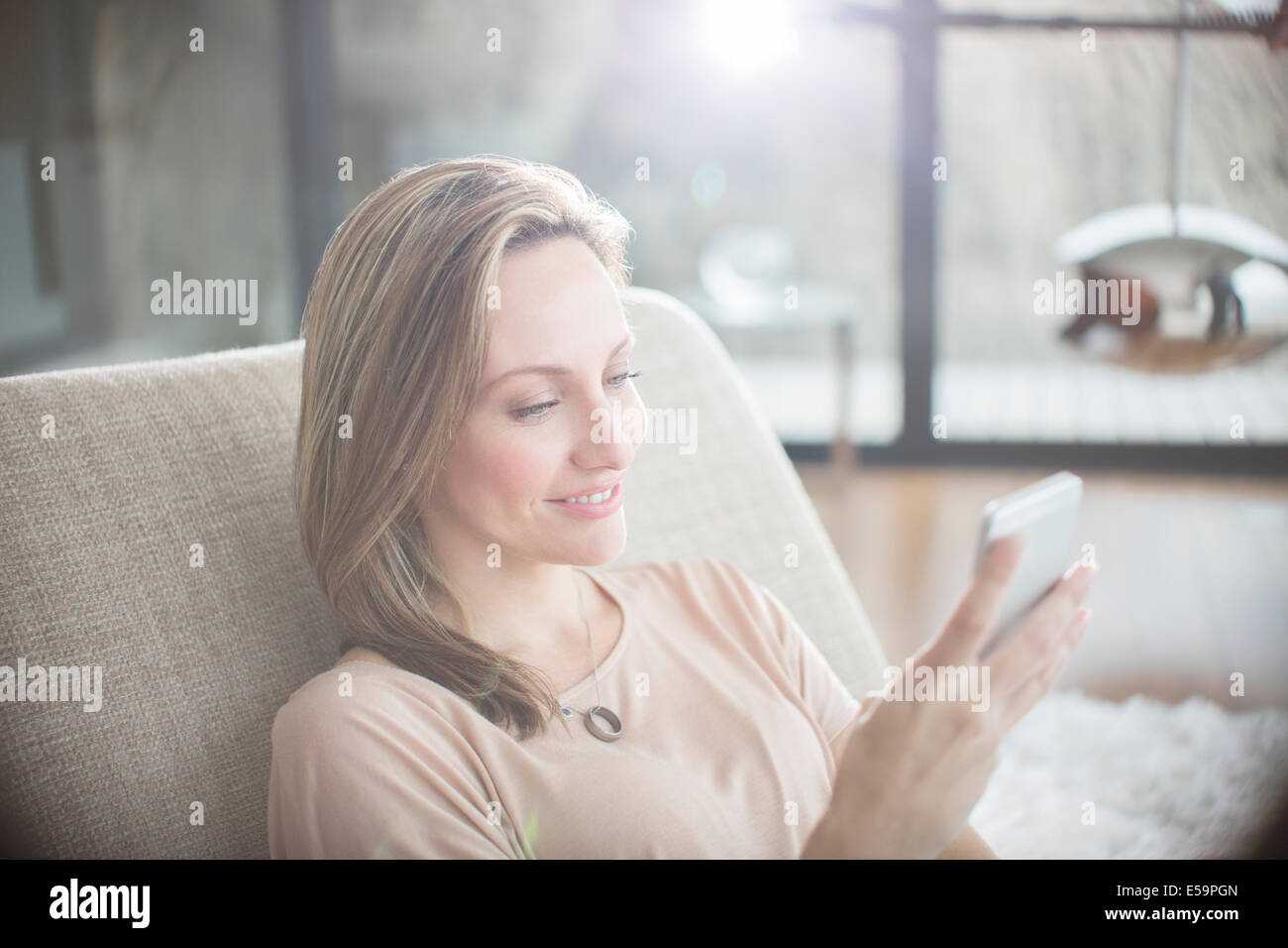 Woman using cell phone on sofa - Stock Image