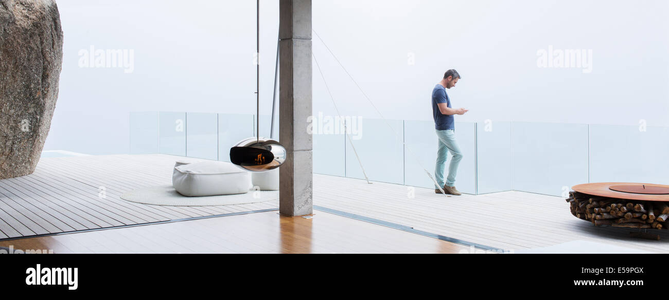 Man using cell phone on balcony of modern house - Stock Image