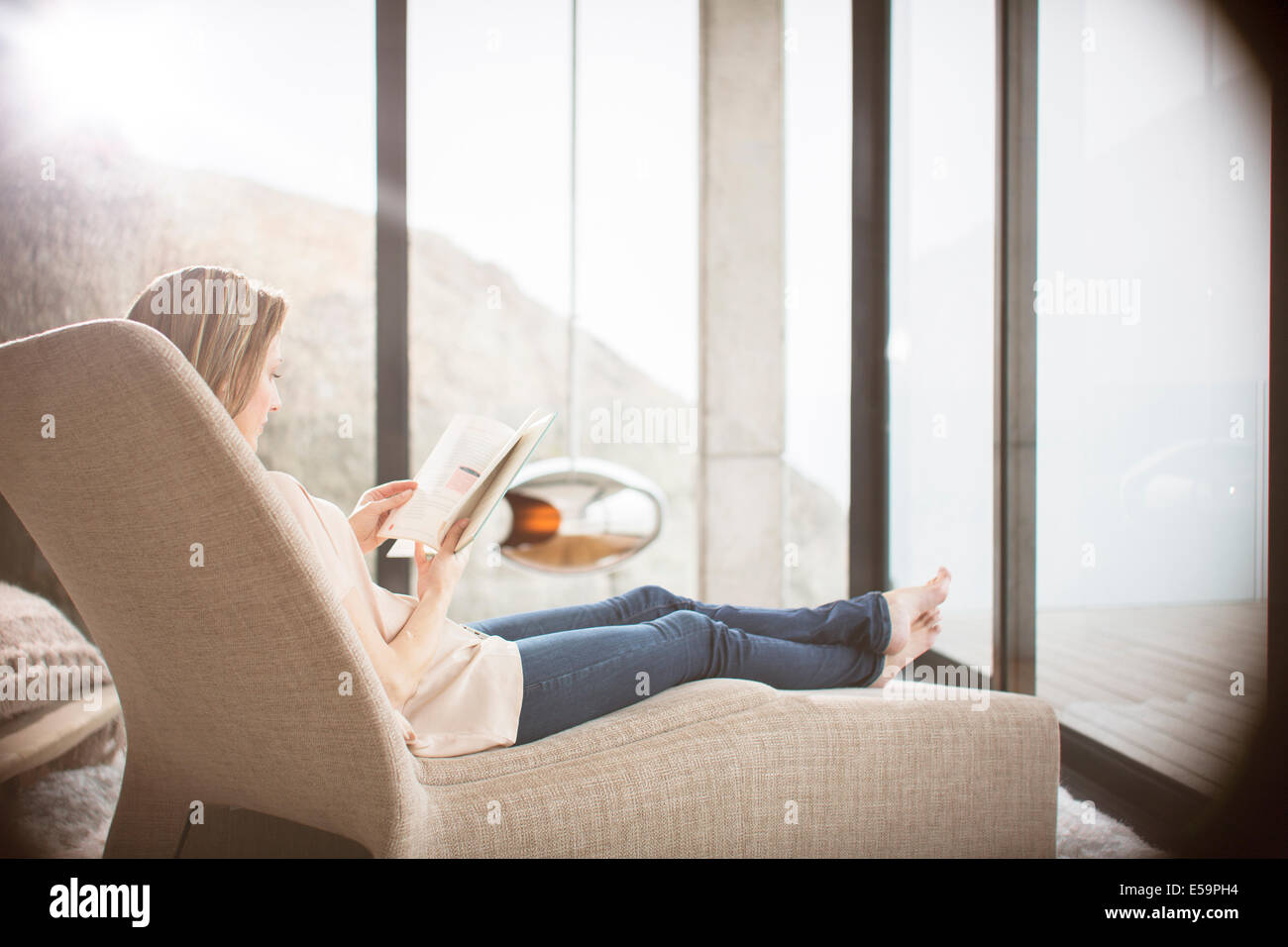 Woman reading on sofa in modern living room - Stock Image