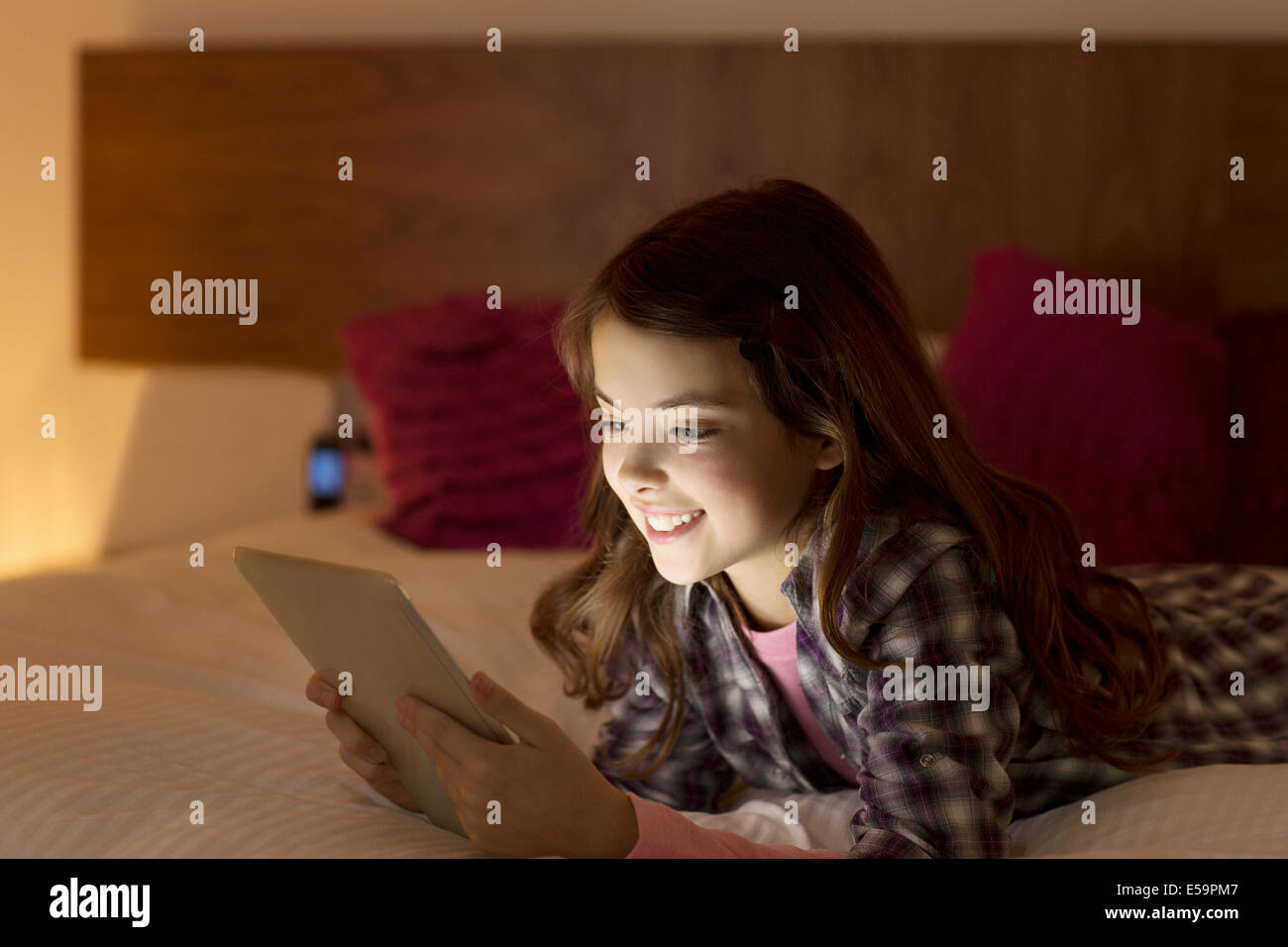 Girl using digital tablet on bed - Stock Image