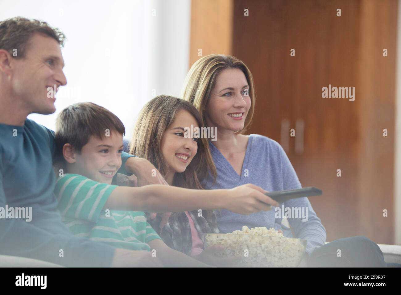Family watching television in living room - Stock Image