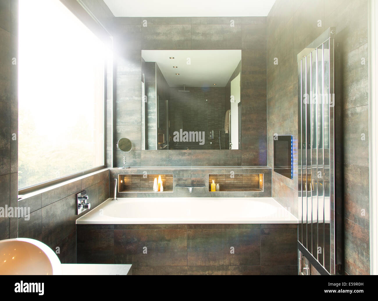 Bathtub and mirror in modern bathroom - Stock Image