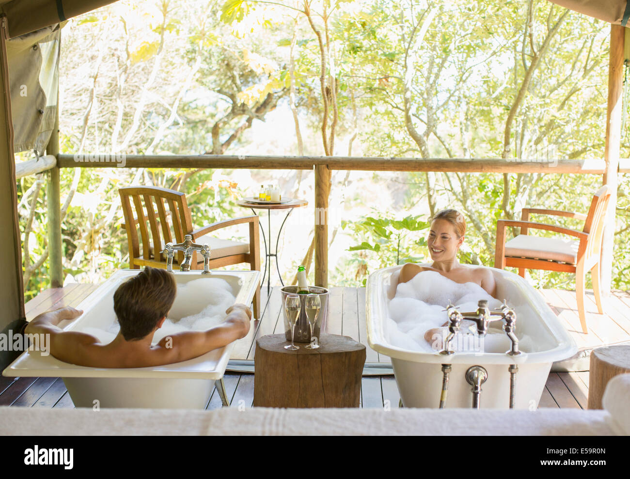 Couple in twin bathtubs in outdoor spa Stock Photo